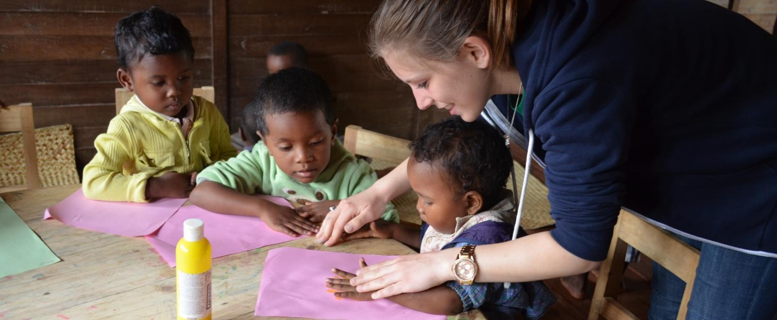 Children get help with an arts and crafts activity from a volunteer doing childcare work in Africa.